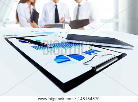 Close-up of business document in touchpad lying on the desk office workers interacting in the background