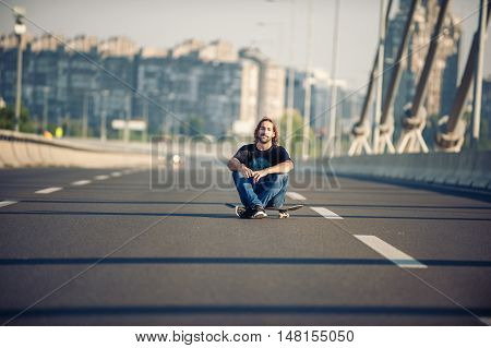 Skateboarder Sitting On His Skateboard At Highway Bridge