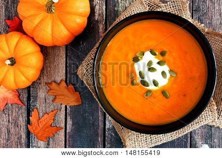 Pumpkin Soup Topped With Pumpkin Seeds And Cream, Overhead Scene On Rustic Wood With Autumn Leaves