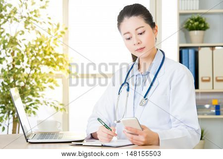 Doctor Recording Patient's Condition By Smart Phone And Computer