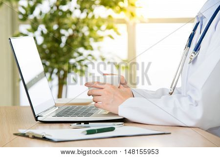 Doctor Using Computer To Research Internet And Drink Coffee