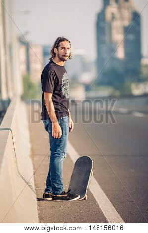 Skateboarder Standing On The City Road Bridge