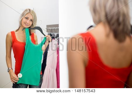 Young woman shopping in a fashion store - Trying on the garments she likes (color toned image; shallow DOF)
