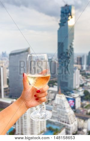Wine in the hand hold asian women and dine in the bangkok city background.