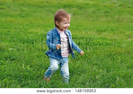 Baby girl walking on the grass (1 year old)