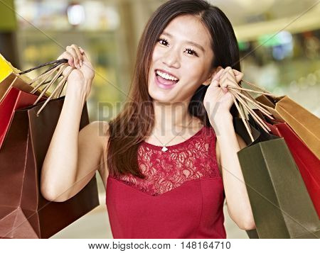 young asian woman on shopping spree carrying paper bags walking in mall happy and smiling