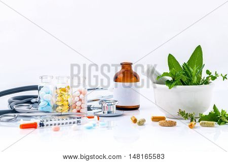 Herbal medicine VS Chemical medicine the alternative health care isolate on white background. White mortar and pestle with fresh herbs and herbal capsules. Stethoscope with fish oil medicine and syringe.