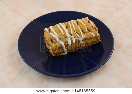Cherry strudel with frosting on blue breakfast plate on tablecloth