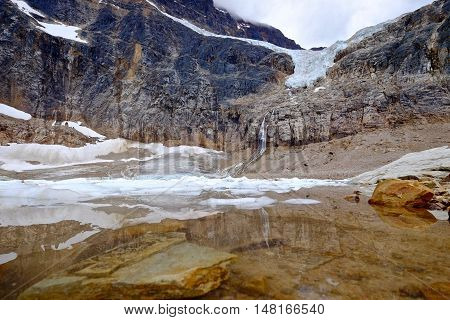 Clear water in alpine lake with rocks and icebergs. Angel Glacier at Mount Edith Cavell. Jasper National Park. Canadian Rockies. Alberta. Canada.