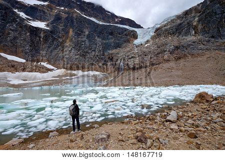 Man ecologist watching melting glacier. Angel Glacier at Mount Edith Cavell. Jasper National Park. Canadian Rockies. Alberta. Canada.
