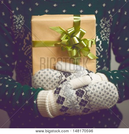 Girl holds in hands Christmas present. Christmas background. Gifts for men. Knitted mittens. Knitted dress. 2017 year. Box with gifts. Merry Christmas. Toned image.