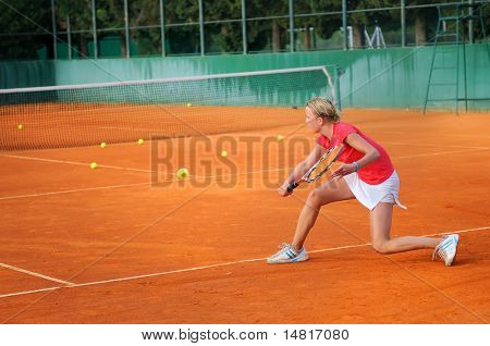 Girl playing tennis outdoor on court