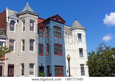 Luxury row houses in Shaw neighborhood in Washington DC. Colorful remodeled townhouses under a blue sky.