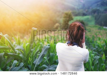 Rear view of female nature photographer in morning.