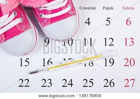 Thermometer And Shoes For Newborn On Calendar, Expecting For Baby
