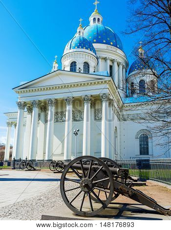 The great building of Trinity Cathedral decorated with colonnades on each side and the golden stars on domes with the old Turkish cannons in front St Petersburg Russia.