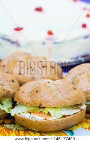 Close up of club salmon sandwiches arranged over a table at an open air garden party. Delicious cake in the background.