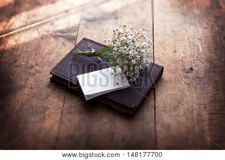 Vintage book and a small bouquet of baby's breath flowers and a blank sheet of folded white paper, on a well used old desk or wooden surface. Intentionally shot with strong shadows and low key.