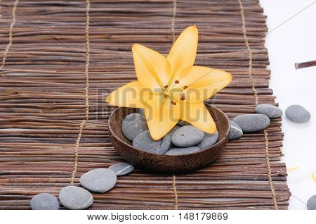Yellow flower with gray stones in bowl on mat