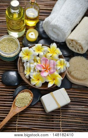 wooden bowl in frangipani with spa set on mat
