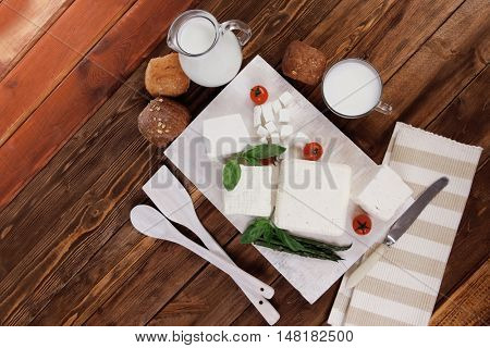 fresh white greek feta cheese with milk in jar basil cherry tomato asparagus and french bun on cutting board over dark wood table