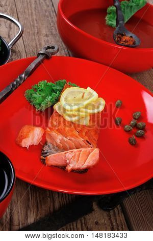 delicious portion of fresh roast salmon fillet on red plate with green salad kale tomato soup bbq sauce and black coffee  - healthy food, diet cooking concept  over wooden table