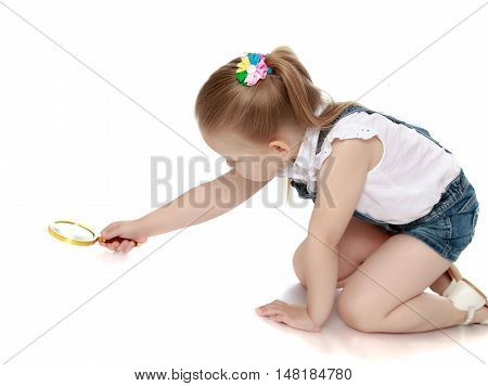 Curious little girl with long blond hair and a short denim jumpsuit. Girl with a magnifying glass looking at something on the floor - Isolated on white background