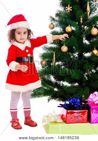Adorable little curly-haired girl, dressed as Santa Claus decorates a Christmas tree toys.Isolated on white background.