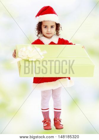 Cute little girl in a coat and hat of Santa Claus, holding a big green box , tied with a bow.white-green blurred abstract background with snowflakes.