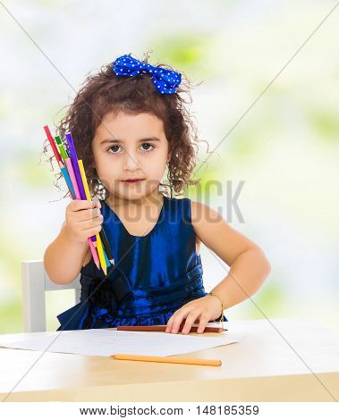 Cute little girl in blue dress, holds a lot of pencils . She paints at a table in a Montessori kindergarten.white-green blurred abstract background with snowflakes.