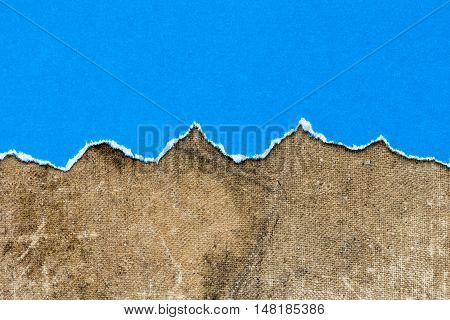Torn blue paper on dirty canvas background