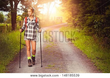 Young woman hiking on country road