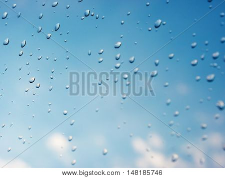 Water drops of rain on blue glass background. Rain drops on window. Shallow DOF.