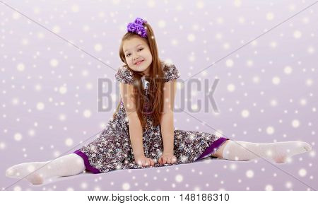 On the Christmas background with white snowflakes.Caucasian little girl with a big purple bow on her head. Girl shows how to do the splits.