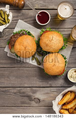 Burgers and cheeseburger on wooden table with sauces fries pickles and lager beer overhead view with copy space