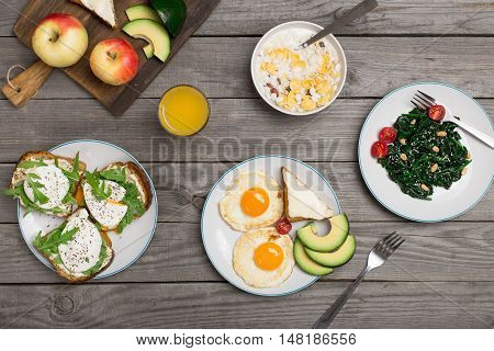 Helpful and tasty breakfast from different of dishes - fried egg avocado cheese sandwiches poached eggs spinach salad muesli and orange juice on wooden table top view