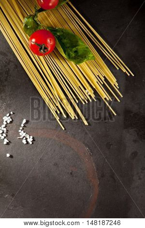 Pasta Ingredients - Tomato and Basil Leaf over Black Slate Background