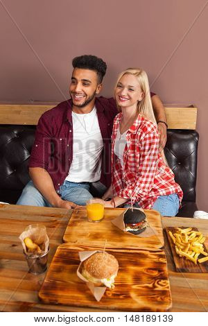 Young Woman And Hispanic Man Sitting In Cafe Hold Orange Juice Order Beef Burger Served In Paper On Wooden Table, Happy Smiling Girl And Guy Couple Fiends Meeting