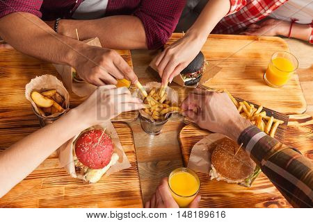 People Group Friends Hands Eating Fast Food Burgers Potato Drinking Orange Juice, Cafe Wooden Table Top Angle View