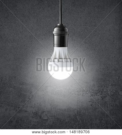 Glowing LED bulb on grunge dark wall