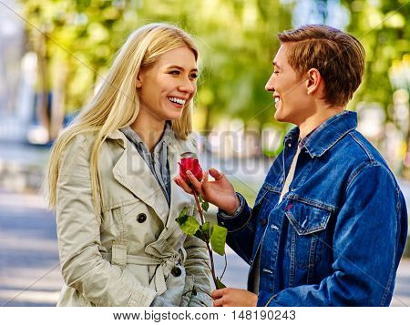 Young couple in love into autumn park . Couple keeps red rose flover. Man gives a girl scarlet rose. Yellow autumn park background.