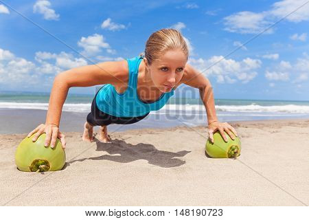 Woman fitness exercise push up on raw green coconut to keep fit and health. Ocean beach surf background. Healthy lifestyle morning workout sport activity on summer family holiday in tropical island.
