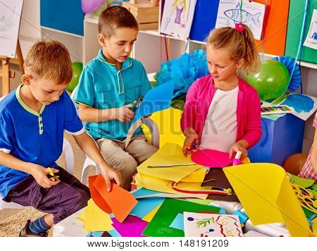 Children are making something out of colored paper on table in primary school. Children craft lesson in primary school. Development children craft at class in school. Independent work.