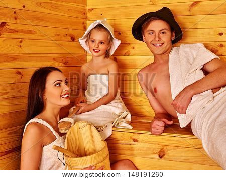 Happy family with child in hat relaxing at sauna. Mother father and children relaxing in sauna.