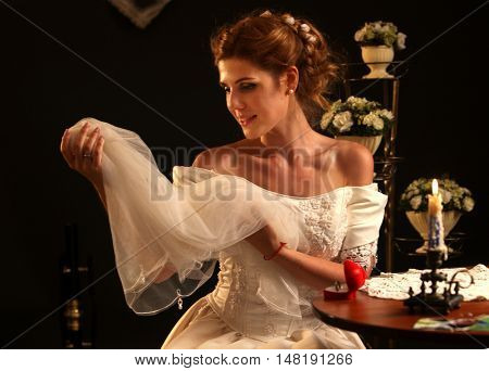 Happy girl in wedding dress sits at table and trying on veils. On table box with wedding ring and burning candle looking down on wedding dress.