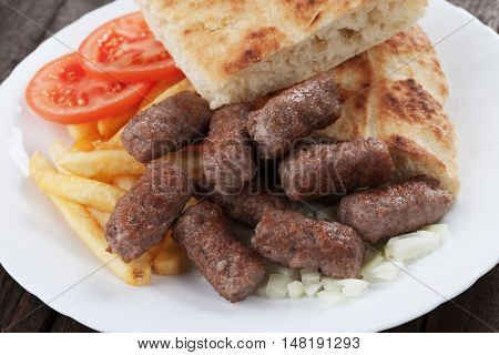 Cevapcici, bosnian minced meat kebab with french fries and somun bread