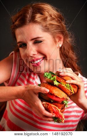 Girl keeps hamburger hamburger fast food. Hamburger is tasty fast food. Girl mischievously winking with one eye.