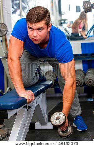 Man working his arms with dumbbells at gym. Sport man with dumbbells looking camera.