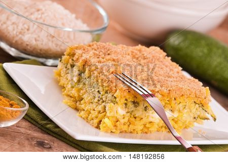 Rice timbale with zucchini on wooden table.