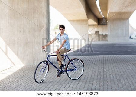 people, style, leisure and lifestyle - young hipster man riding fixed gear bike on city street